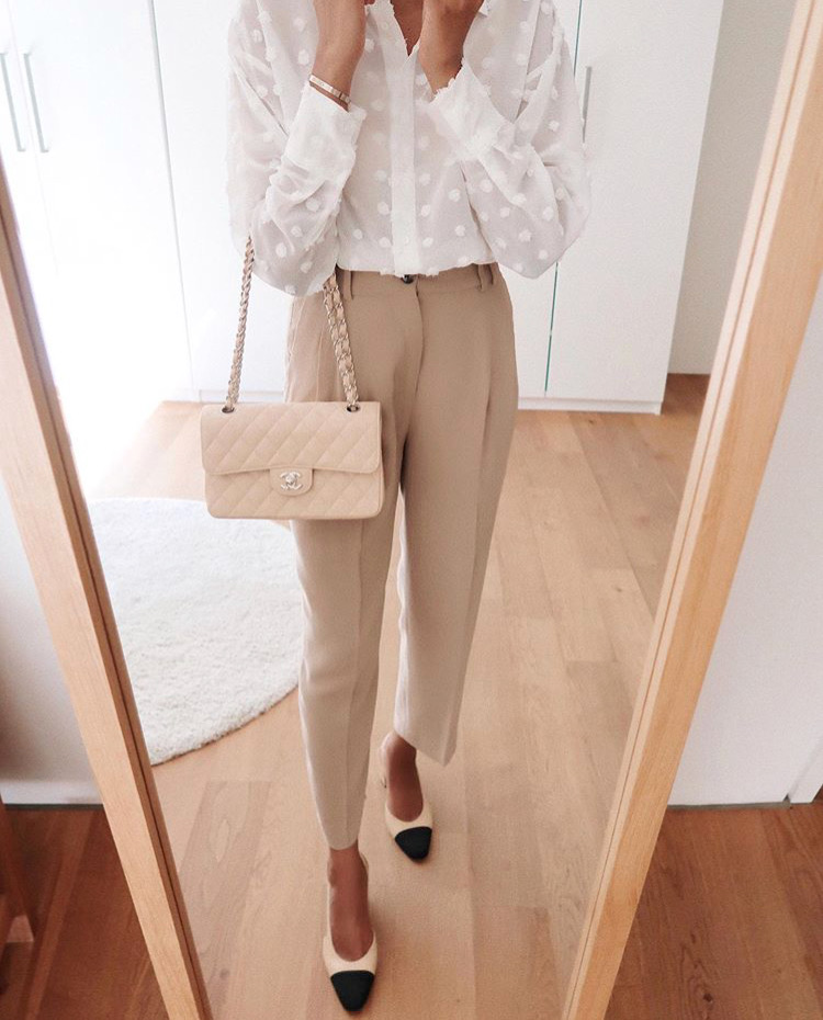 Beige trousers, white blouse, Chanel small flap beige and beige and black Chanel sling backs.